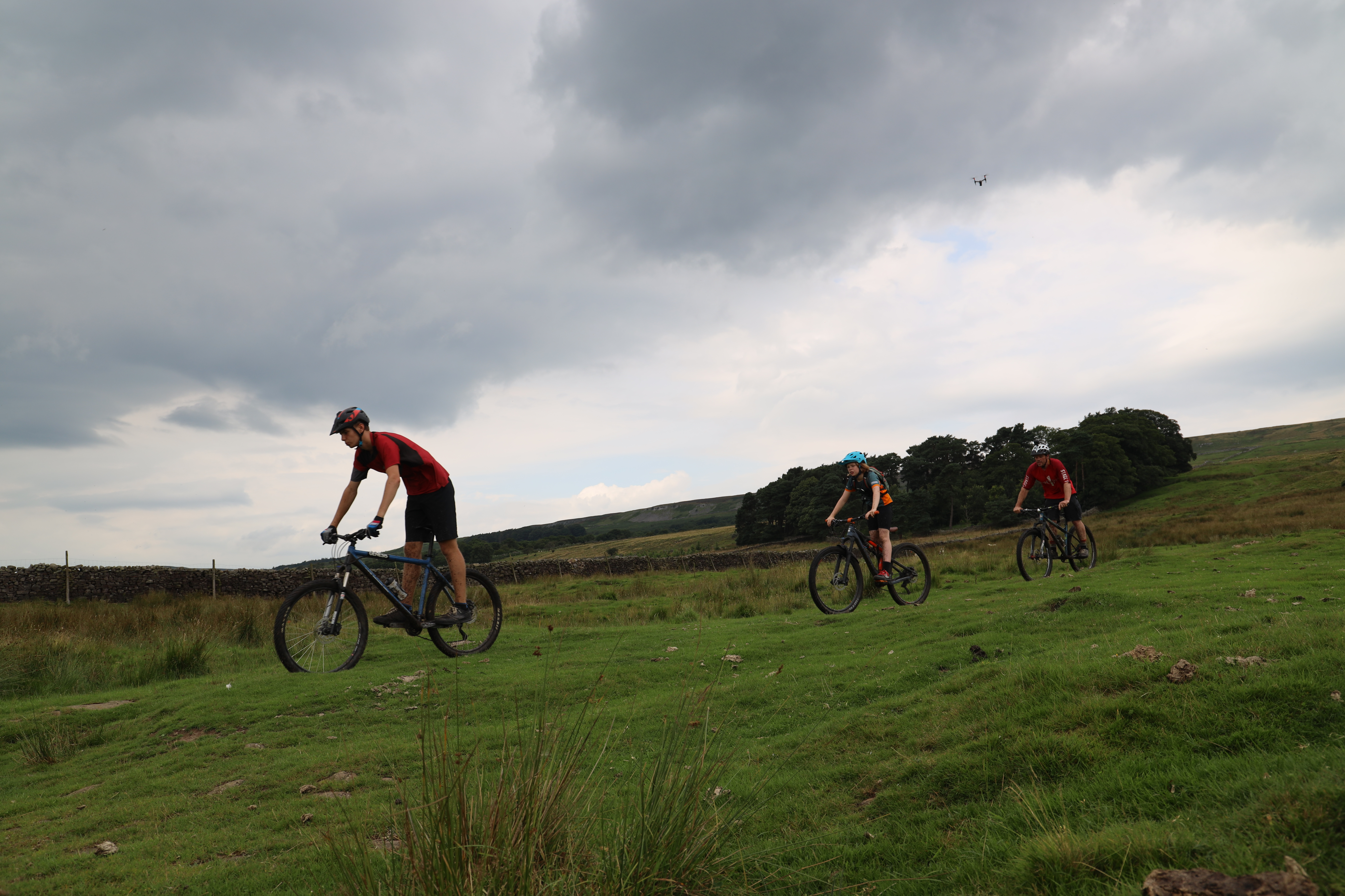 Three mountain bikers ride down a grassy hill in the Dales, for Cycle the Dales promotional video with Pocket Projects